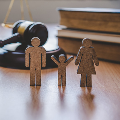 cardboard family cutout in front of gavel and books